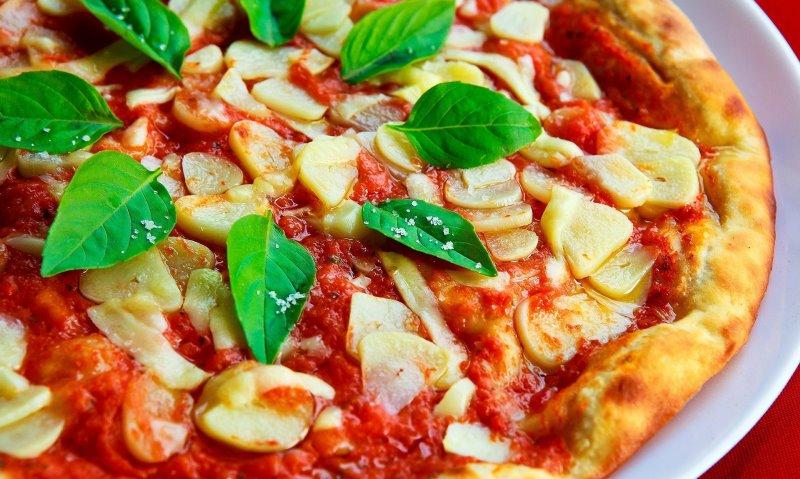 Pizza mit Knoblauchscheiben und Basilikum