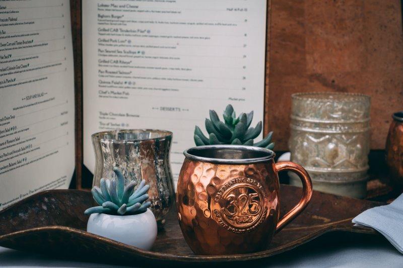 Tasse aus Metall, Pflanzen und eine Karte