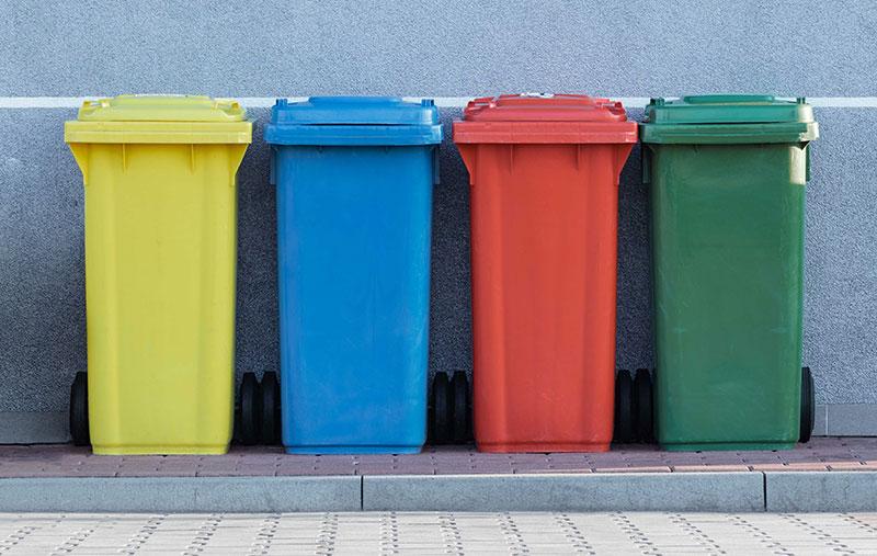 Bunte Abfallsammler auf dem Bürgersteig