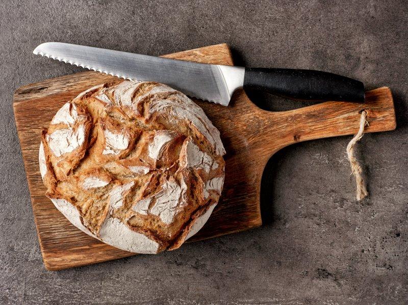 Frischer Brotlaib auf einem Brett neben einem großen Brotmesser
