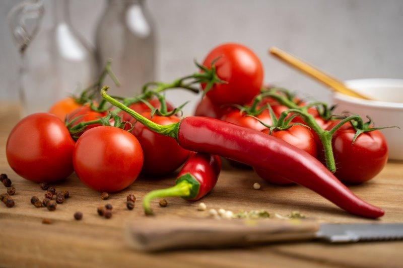 Tomaten und Chilis auf einem Holzbrett mit einem Tomatenmesser.