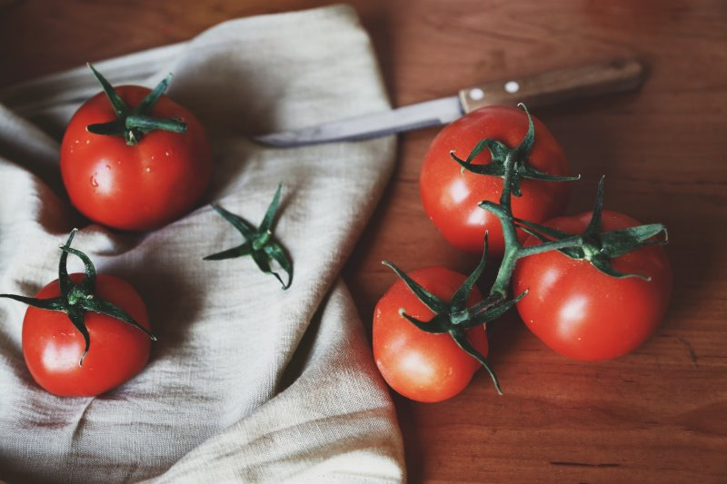Tomatenmesser liegt neben frischen Tomaten auf einem Geschirrtuch.