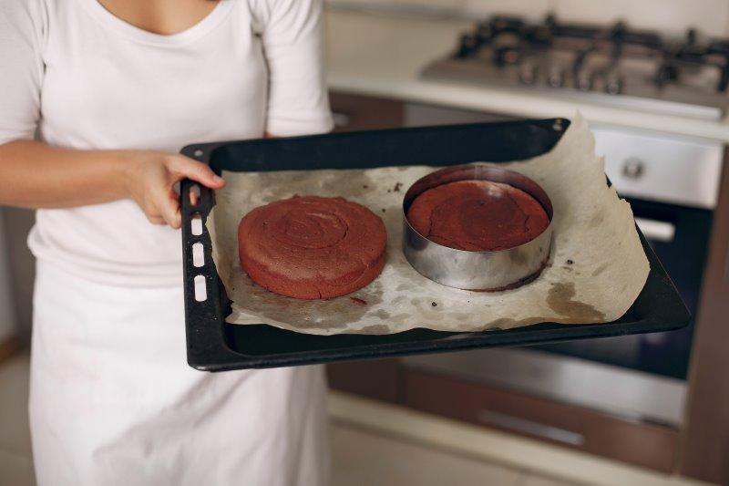 Eine Person hält ein mit Backpapier ausgelegtes Backblech fest, auf dem zwei Tortenböden platziert sind. Der rechte Tortenboden befindet sich in einem Tortenring.