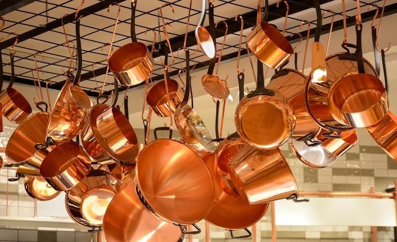 Glänzende Kupferpfannen und Kupfertöpfe.