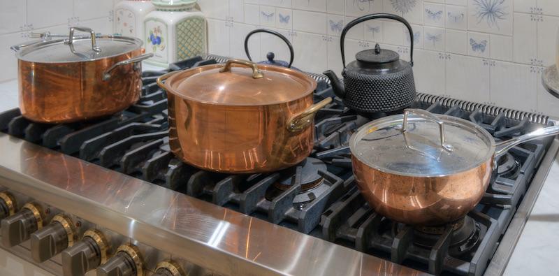 Oval, eckige und runde Kupferpfanne auf einem Gasherd.