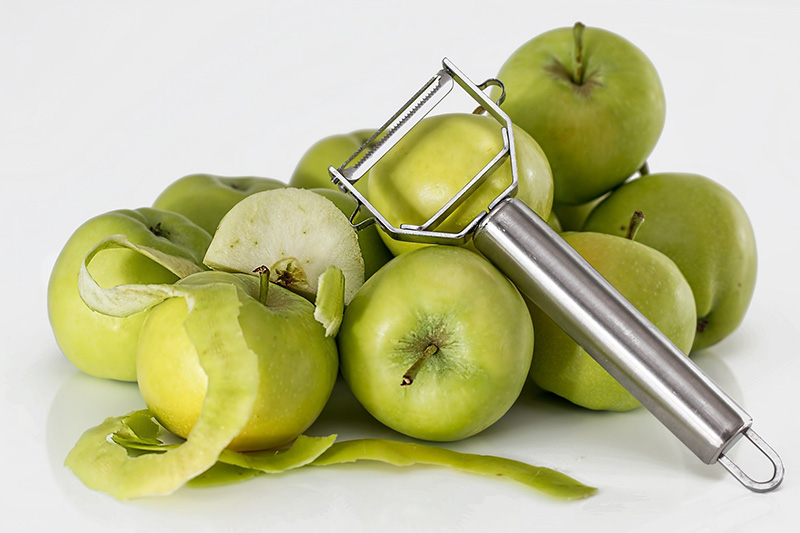 Pendelschäler liegt auf Äpfeln